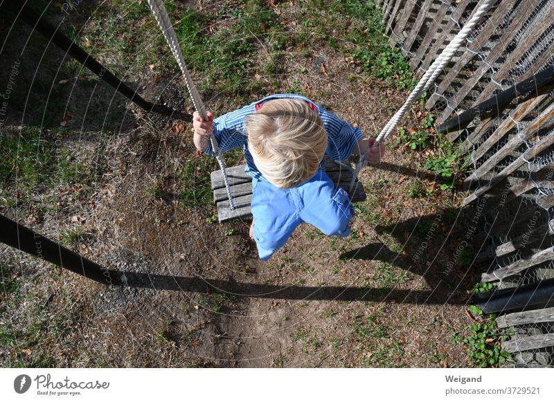 Kind auf dem Spielplatz Kindheit Junge Schaukel kita Kindergarten Grundschule aufwachsen Schwung Freizeit & Hobby schaukeln Außenaufnahme Freude Spielen Mensch