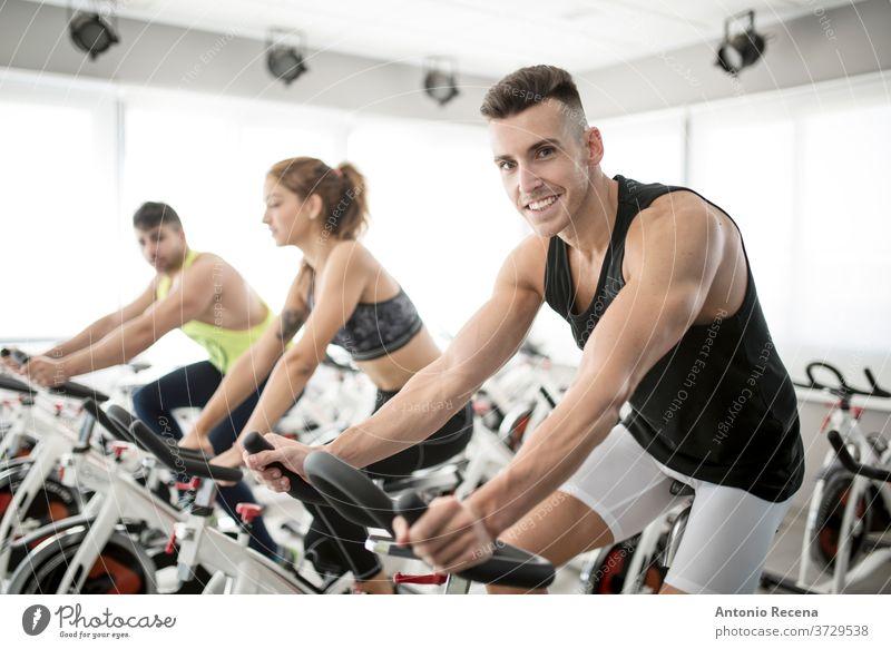 Gruppe von Personen im Spinning-Saal der Turnhalle Übung Fahrrad Fitnessstudio Männer Erwachsener Seitenansicht Schweiß Muskel Tonung Muskelaufbau horizontal
