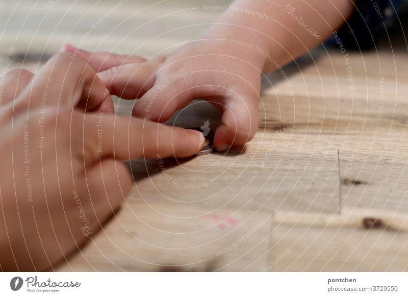 Eine Hand gibt, die andere nimmt. Mutter schiebt ihrem Kind eine Geldmünze über den Holztisch zu. geldmünze kind schieben geben nehmen kosten teuer kindergeld