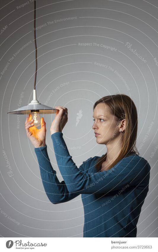 Frau mit einer Glühbirne auf weiß Lampe Brünette Wechsel wechseln tauschen austauschen Idee Konzept weiblich Mode Mädchen Gesicht Eco Porträt grün Hand gut