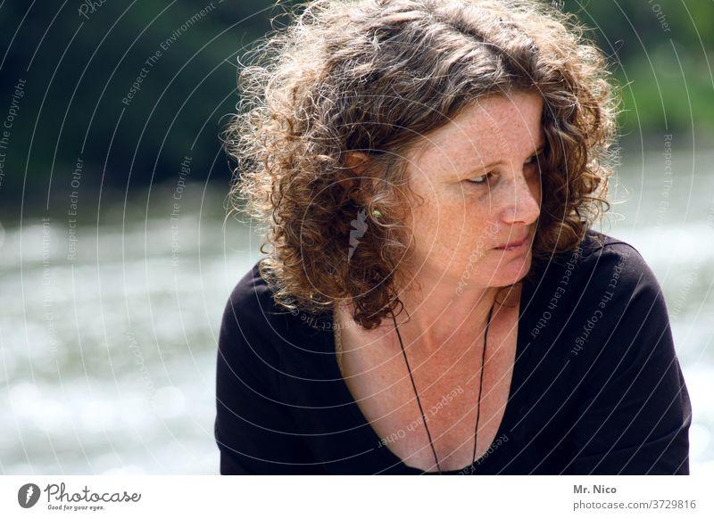 Frau mit Locken und Sommersprossen blickt zur Seite Porträt Portrait feminin schön Dekolleté natürlich Gelassenheit beobachten nachdenklich Ausstrahlung ruhig
