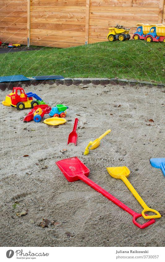 Spielzeug im Sandkasten Spielen Außenaufnahme Farbfoto Kind Freude Kindheit Kindergarten Tag Kleinkind Kinderspiel Freizeit & Hobby Kindererziehung Spielplatz