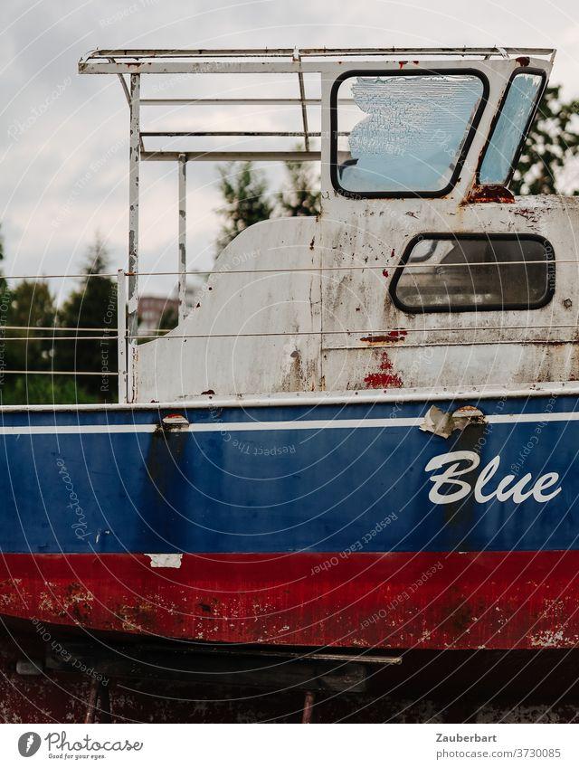 Blue - Seitenansicht und Brücke eines alten Motorboots in rot und Blau Boot blau weiß Heck Rost verrostet Lager Bootslager Bock aufgebockt Schiff