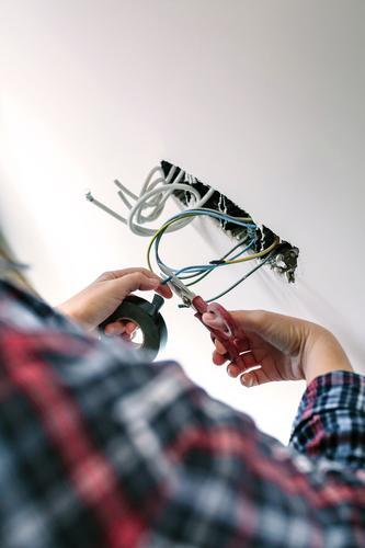 Nicht erkennbarer Elektriker, der an der Elektroinstallation eines Hauses arbeitet Elektromonteur unkenntlich Elektrotechniker Installation Kabel schneiden