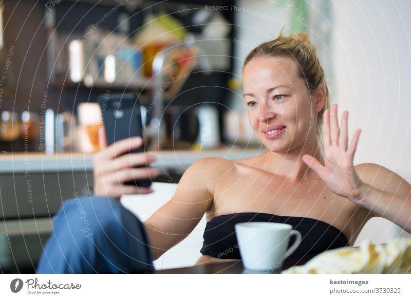 Junge, lächelnde, fröhliche, zufriedene Frau, die zu Hause in der Küche sitzt und soziale Medien auf dem Mobiltelefon nutzt, um mit ihren Lieben zu chatten und in Verbindung zu bleiben. Zu Hause bleiben, sozial distanzierender Lebensstil.
