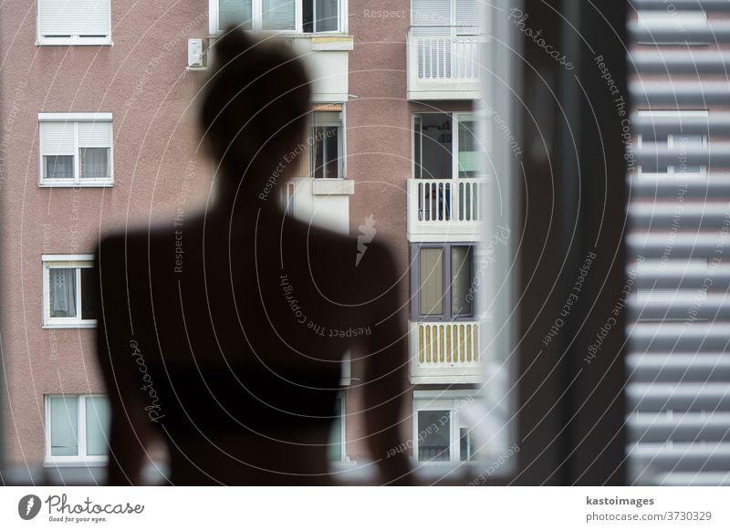 Hausquarantäne und soziale Distanzierung während einer Covid-Pandemie. Silhouette einer einsamen, weißen Frau, die am Fenster steht und ängstlich nach draußen schaut. Coronavirus-Infektion, Pandemien, Krankheitsausbrüche