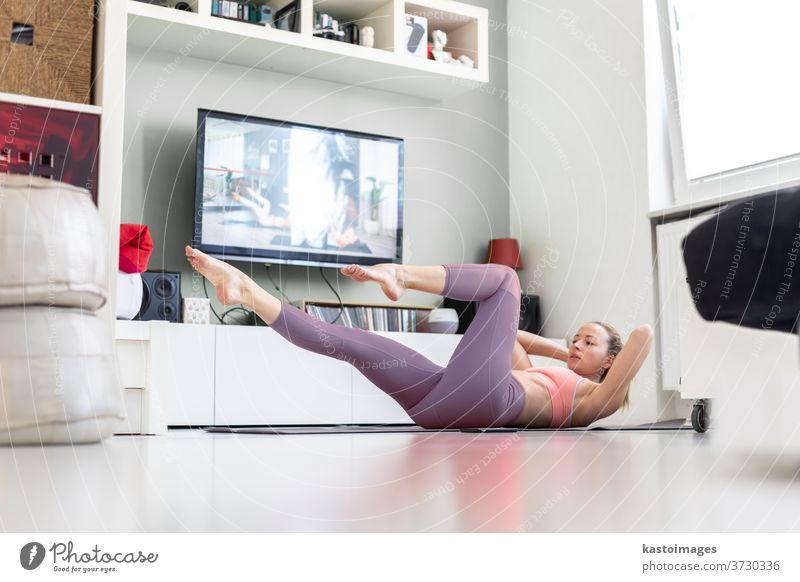 Attraktive sportliche Frau, die zu Hause trainiert und in ihrer kleinen Studiowohnung vor dem Fernseher Pilates-Übungen macht. Soziale Distanzierung. Bleiben Sie während einer Coronavirus-Pandemie gesund und bleiben Sie zu Hause