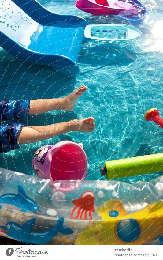 Kleinkind im Planschbecken kleinkind wasseroberfläche schiffchen gießkanne eimer spiel spielzeug wasserspielzeug hitze hochsommer baden wasserbecken