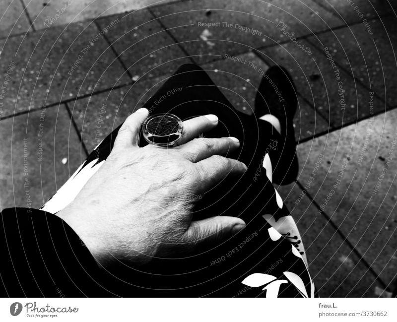 Mittags sitzt die Frau gern in einem Straßencafé, mit Stiefeletten, Ring und auch bei Regen. Muster Rock Füße Leggings Asphalt Bistro Schmuck Hand Modeschmuck