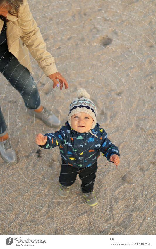 kleines Baby, das unter dem Schutz eines Erwachsenen in den Himmel schaut Porträt Mutterliebe Geborgenheit Sicherheit Freitreppe Wachstum Helfer hilflos