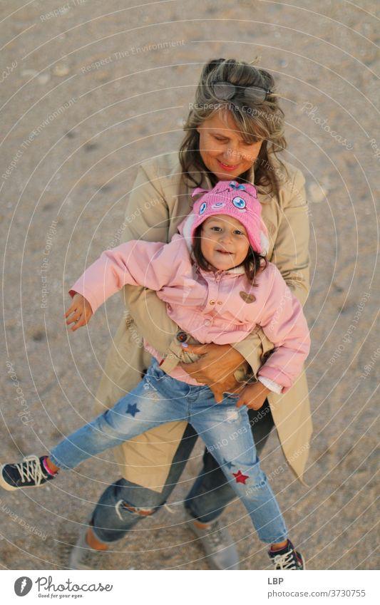 Oma hält kleines Mädchen Porträt Liebe Liebkosen Wahrheit Vertrauen Lebensfreude Fröhlichkeit Gefühle Kindheit Paar Familie & Verwandtschaft Großmutter Senior