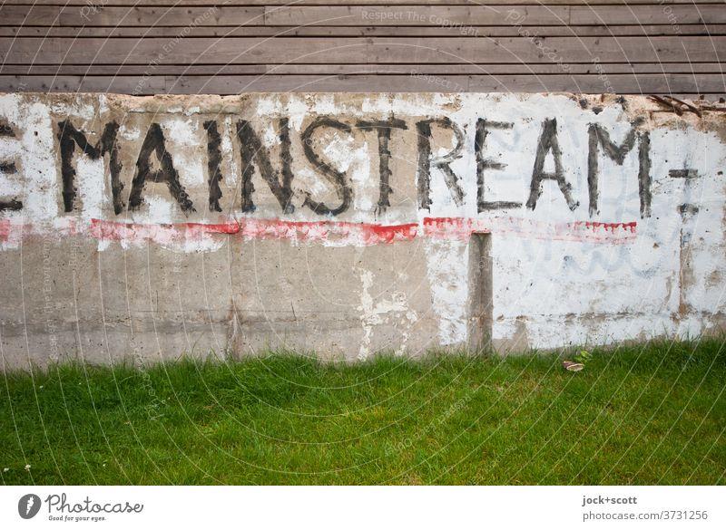 Mainstream auf Fundament Beton Wort Wiese Großbuchstabe Straßenkunst Subkultur Kreativität Holzzaun Anstrich lost places Wand Rest Pinselstrich verwittert