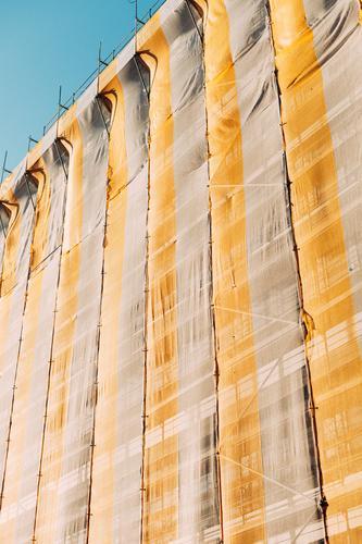 gerüstnetz Gerüst Gerüstnetz Gerüstplane Baustelle Baugerüst Himmel gelb Blauer Himmel hoch Abdeckung Wandel & Veränderung Haus Gebäude Fassade Sanieren Schutz