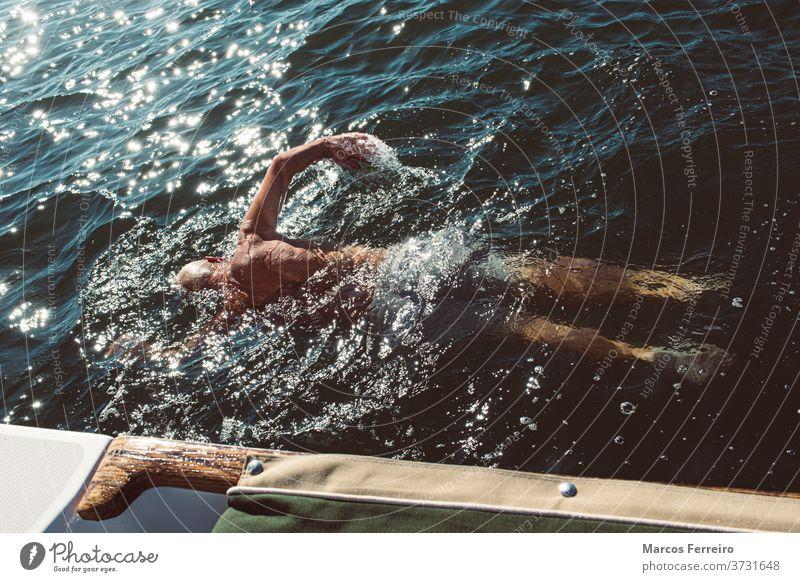 älterer Mann, der neben seinem Boot im Meer schwimmt Erholung Windstille im Freien Europäer Segeln Aktivität Übung Jacht Schwimmsport Tourismus schön Menschen