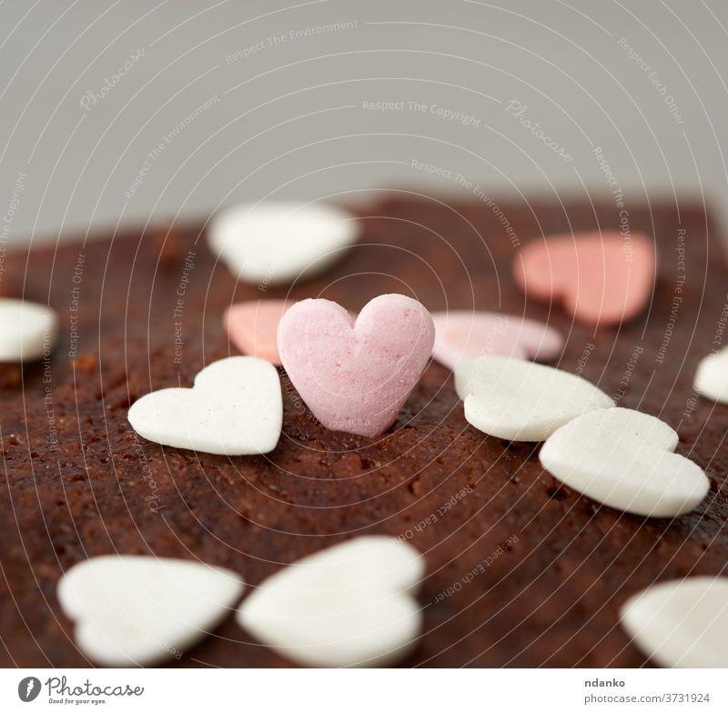 herzförmiger Zuckerguss auf Brownie-Schokoladenkuchen Berieselung Herz braun Kuchen backen gebacken Bäckerei schwarz Nahaufnahme Kakao Essen zubereiten Küche