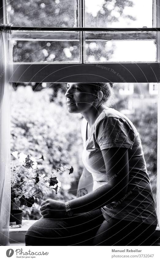 Frau, die zu Hause am Fenster sitzt Person jung Mädchen heimwärts schön Kaukasier Sitzen Lifestyle Menschen Erwachsener weiß im Innenbereich Glück lässig eine