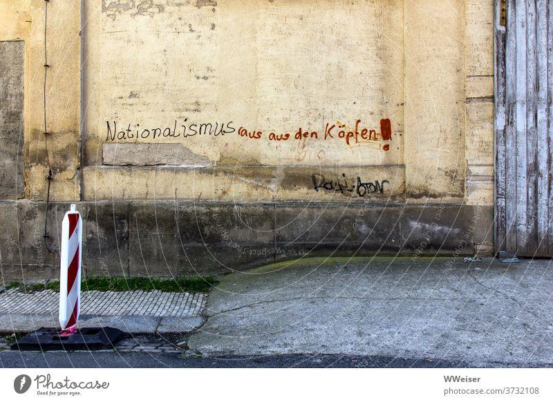 Nationalismus raus aus den Köpfen! - fordert die alte Hauswand Wand Mauer Schrift Parole Nazis raus Rechte Antifa Kleinstadt Landhaus Aufschrift Forderung