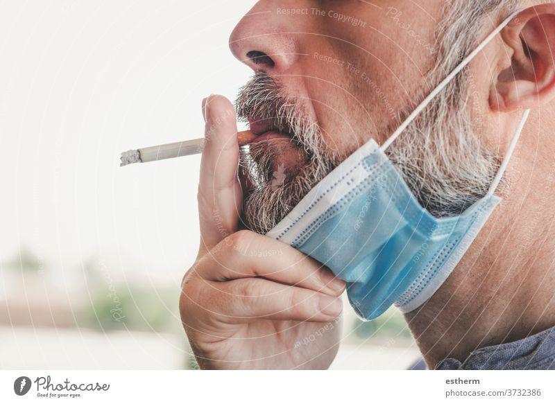 covid-19,Mann mit medizinischer Maske, der auf der Strasse eine Zigarette raucht Coronavirus 2019-ncov ungesund Rauch Virus Seuche medizinische Maske Verbot