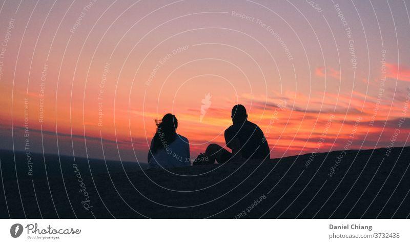 Paar mit Pink Sky Sonnenaufgang Sonnenaufgang - Morgendämmerung rosa Stimmung Rücken Schattenspiel Sonnenuntergang Sonnenstrahlen Sonnenlicht Farbfoto