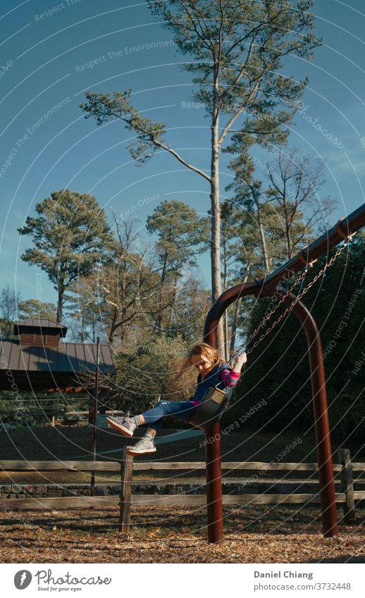 Kleines Mädchen Schaukel Kind pendeln Freude schaukeln Spielplatz lachen Spielen Kindheit Leben Winter fröhliches Kind Außenaufnahme 1 Fröhlichkeit