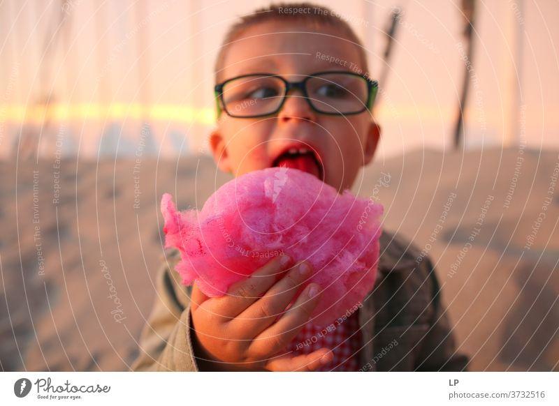 Junge isst rosa Zuckerwatte Blick Vorderansicht Oberkörper Porträt Sonnenlicht Außenaufnahme mehrfarbig unschuldig Unlust Überleben Perspektive Neugier