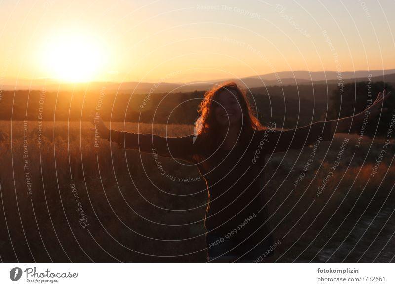 Frau mit offenen Armen vor roter Landschaft mit Sonnenuntergang Lebensglück glücklich Fröhlichkeit Glück Lebensfreude Freude Zufriedenheit Mensch