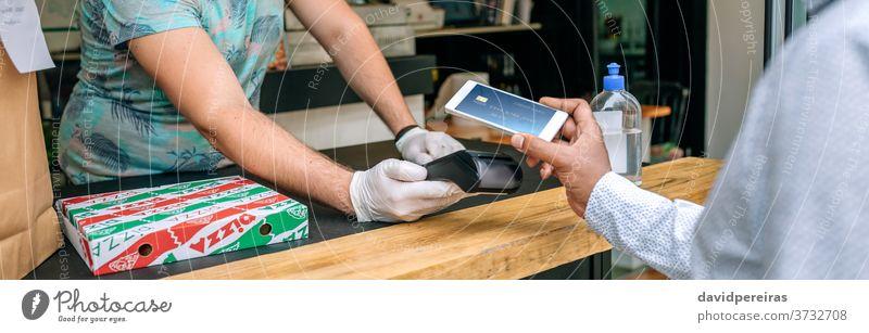 Mann bezahlt mit dem Handy eine Essensbestellung zum Mitnehmen bezahlen Mobile wegnehmen Lebensmittel nfc Pos-Terminal Transparente Netz Panorama Kopfball