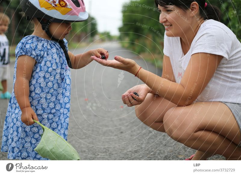 Mutter bietet ihrem Kind ein Stück Obst an Porträt Liebe Wahrheit Vertrauen Lebensfreude Fröhlichkeit Gefühle Kindheit Paar Familie & Verwandtschaft Geschwister