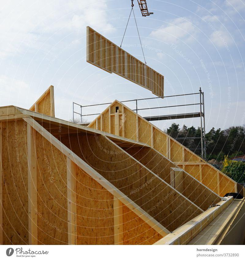 Holzbau Baustelle: Wand am Kran Holzhaus Holzrahmenbau Zimmerei Zimmermann Rohbau OSB-Platten Balken Dachgiebel Architektur Außenaufnahme Gebäude Bauwerk