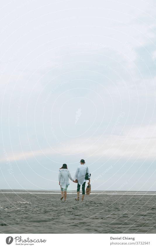 Paar zu Fuß auf dem Strand Verliebtheit verwandt stimmig Zuneigung Vertrauen Sandstrand Schönes Wetter Liebespaar Zusammensein Reisefotografie Blauer Himmel