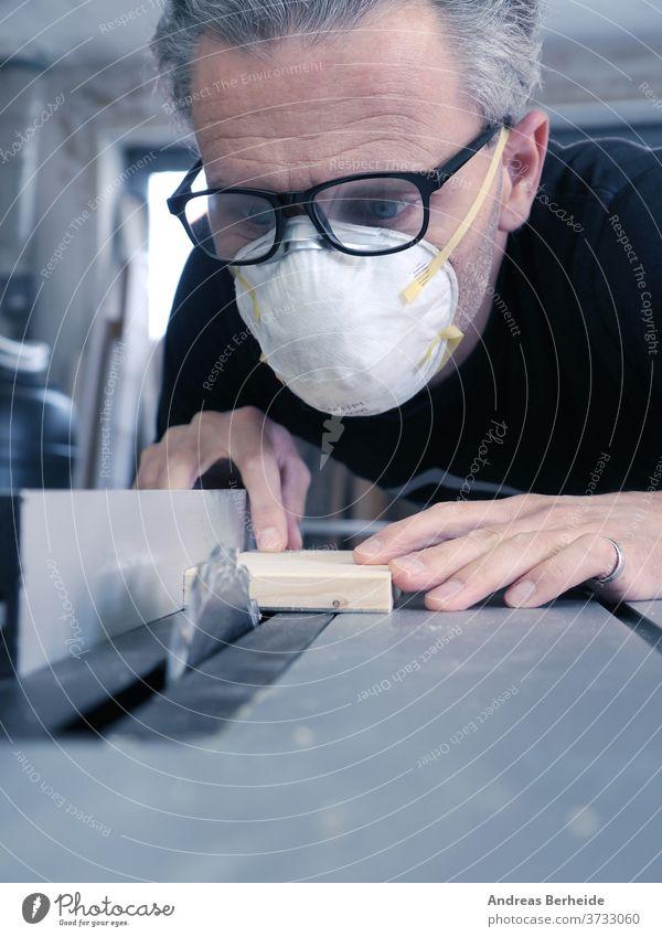 Mann mit Staubmaske und Schutzbrille bei der Arbeit an einer Kreissäge Werkzeuge Maschine Heimwerker Arbeiter Herstellung Aktivität schützend beruflich