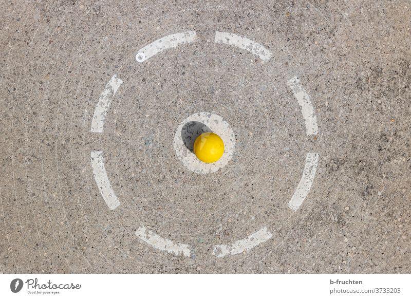 gelber Minigolfball wartet am Abschlagpunkt Spiel Freizeit & Hobby Spielen Außenaufnahme Freude Erfolg Loch rund Golfball warten Mitte zentriert zentral