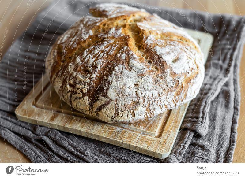Frisch gebackener Brotlaib mit Kruste auf einem Holz Schneidebrett frisch knusprig geschirrtuch Lebensmittel rustikal Bäckerei Frühstück Gesunde Ernährung