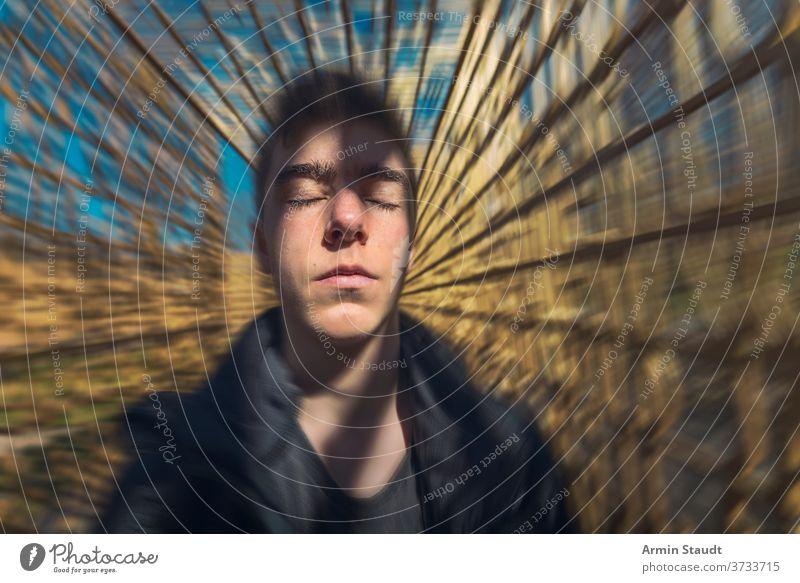 Porträt eines träumenden jungen Mannes mit bewegtem Hintergrund Meditation Konzentration Vorstellungskraft Inspiration ernst schön gutaussehend dynamisch