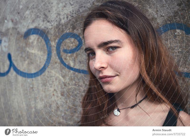 """Porträt einer lächelnden jungen Frau mit dem Wort """"we"""" an einer Wand Teenager Mädchen lässig Kaukasier im Freien Lächeln glücklich Glück schön lange Haare"""