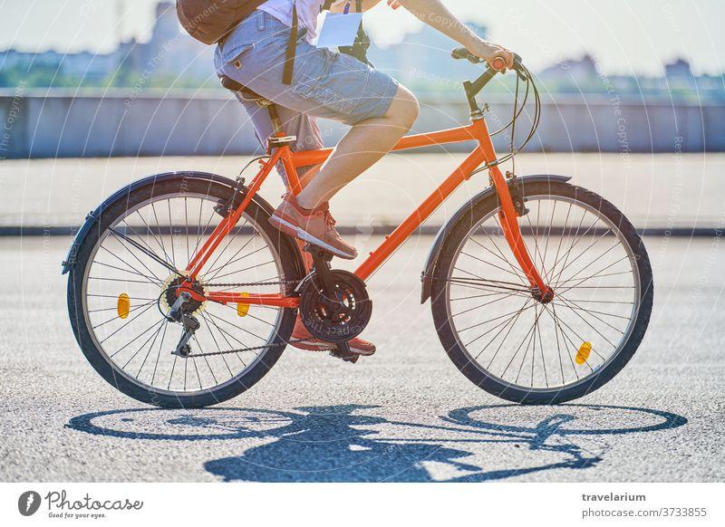 Junge Frau fährt auf einem Fahrrad auf der Stadtstraße Mädchen Großstadt Mitfahrgelegenheit Straße Radfahrer Reporter Plakette Fotokamera Rucksack Sonnenlicht