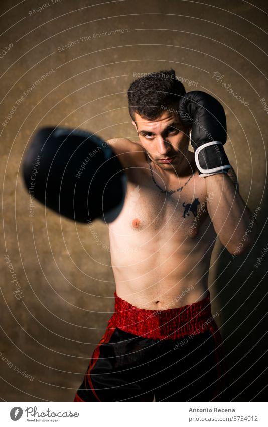 Junger Mann, der in der Studioaufnahme posiert. Thai Boxer Schweiß kämpfen Kick Unterarme Gewalt Kraft stark männlich wettbewerbsfähig kardiovaskulär Kämpfer