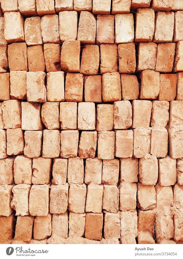 Ein Stapel roter Ziegelsteine füllt den Rahmen aus, in dem in Indien gebaut wird dreckig alt Zement altehrwürdig Beton Design Hintergrund Maurerhandwerk