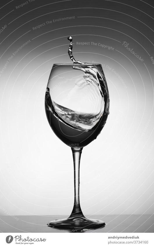 Weißweinspritzer auf grauem Hintergrund. Silhouette eines Glases. selektiver Fokus Wein trinken platschen weiß Restaurant Wasser Objekt Kristalle liquide