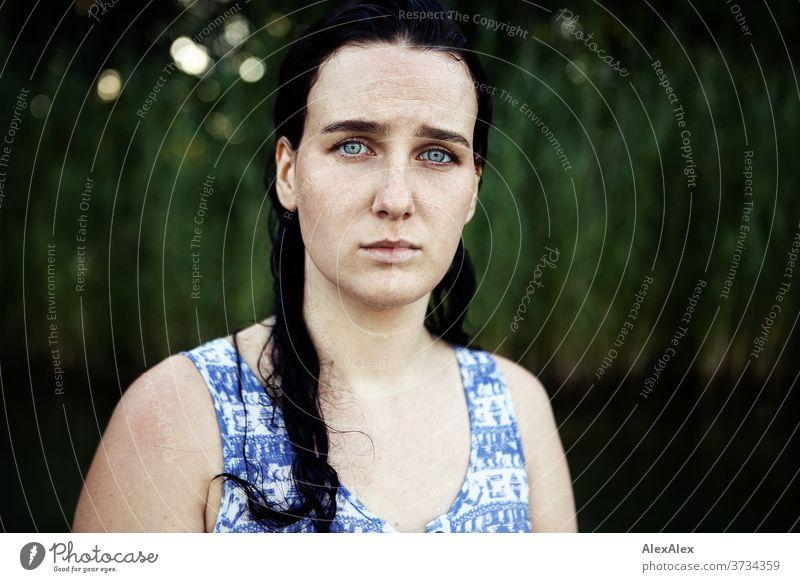 Nahes Portrait einer sommersprossigen Frau mit nassen Haaren in einem See vor Schilf schönes Wetter Stimmung selbstbewußt baden Kleid nasse haare weiblich