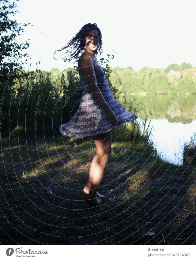 Nahes Portrait einer jungen Frau an einem Seeufer in der Natur mit Licht und Schatten durch Bäume schönes Wetter Stimmung selbstbewußt Kleid nasse haare