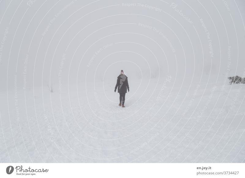 Spaziergang im Schnee Schneelandschaft Mensch Frau Junge Frau alleine einsam Einsamkeit Kälte kalt eisig Frost Eis Nebel Schneedecke Winter Winterurlaub