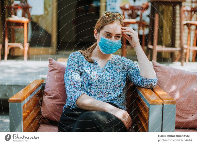 Junge Frau mit Maske draußen im Coffeeshop denkt 2020 Erwachsener schön Kaffee Kaukasier Großstadt Kaffeehaus Konzept Coronavirus covid-19 alltägliches Leben