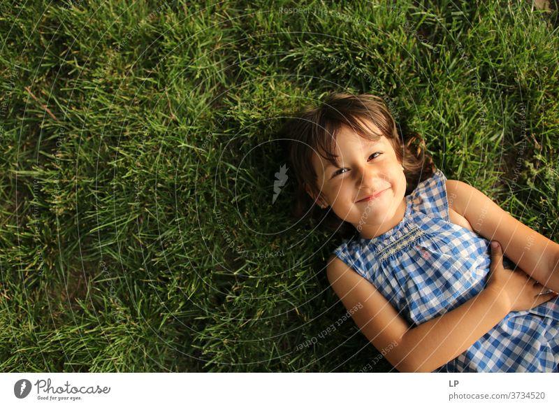 Mädchen lächelt in die auf dem Gras liegende Kamera Oberkörper Porträt Textfreiraum links Strukturen & Formen Muster abstrakt Außenaufnahme Gedeckte Farben