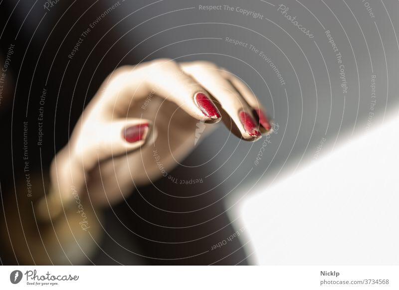 linke Hand einer Schaufensterpuppe mit roten Fingernägeln im Lichtspiel zwischen Licht und Schatten Fingernagel Nagel feminin Puppe Nagellack dunkelrot weiß