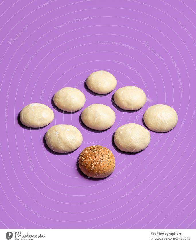 Brötchen gebacken und rohe Teigkugeln isoliert auf violettem Teig. Herstellung von Burgerbrötchen ausgerichtet Hintergrund Bäckerei Bälle hell Essen zubereiten