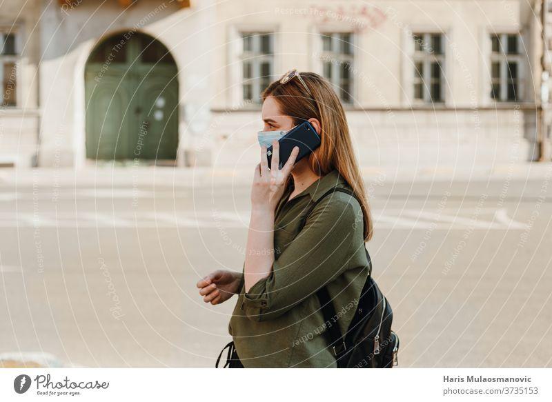 Frau mit Gesichtsmaske telefoniert draußen, Profilansicht 2020 Erwachsener schön blau Kaffee Kaukasier Kind Kindheit Großstadt Konzept Coronavirus covid-19