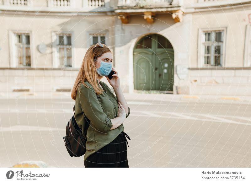 Junge Frau mit Maske telefoniert draußen in der Stadt 2020 Erwachsener schön blau Kaffee Kaukasier Kind Kindheit Großstadt Konzept Coronavirus covid-19