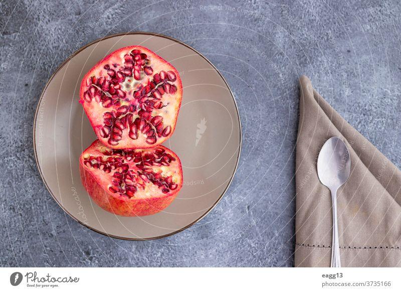 In die Hälfte geschnittene und auf einem Teller servierte Granatapfelfrucht Antioxidans Antioxidantien Hintergründe Schönheit Schalen & Schüsseln schließen