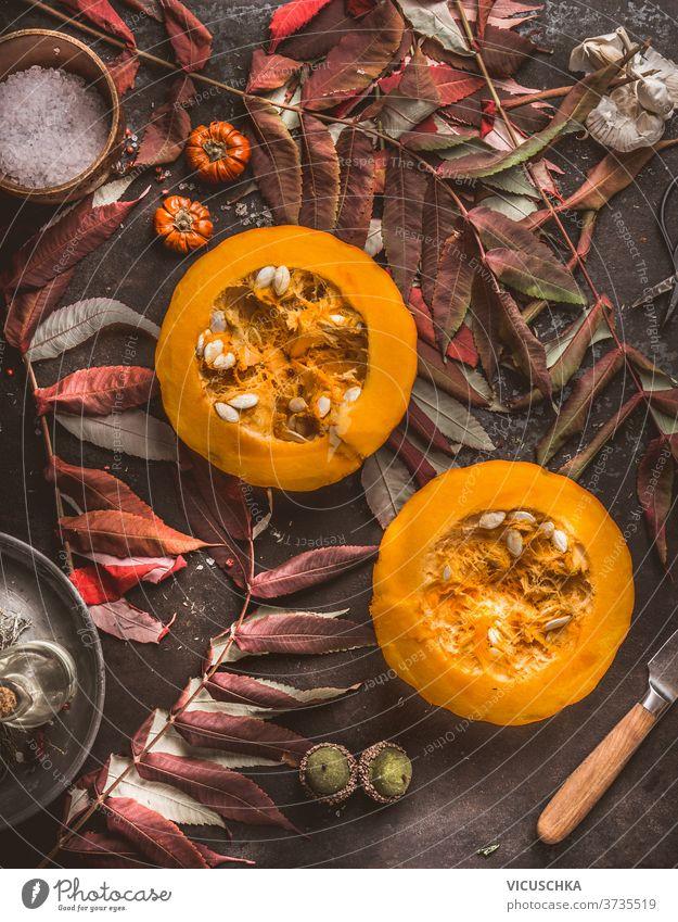 Saisonale Lebensmittel. Halber Hokkaido-Kürbis mit Samen, Messer und Herbstlaub auf dunklem Küchentisch. Herbstliche Stimmung. Ansicht von oben